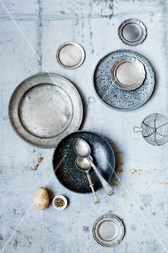 Pewter plates, bowls and spoons on a vintage surface