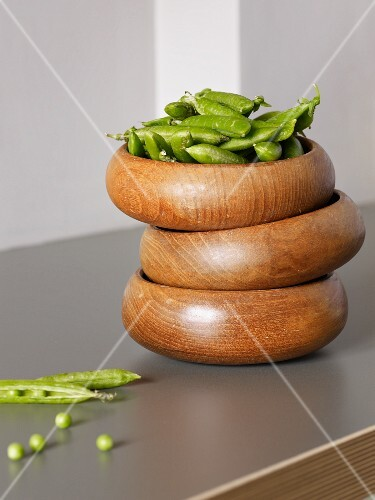 Fresh pea pods in a stack of wooden bowls