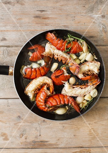 Fried lobster tails with garlic in a pan