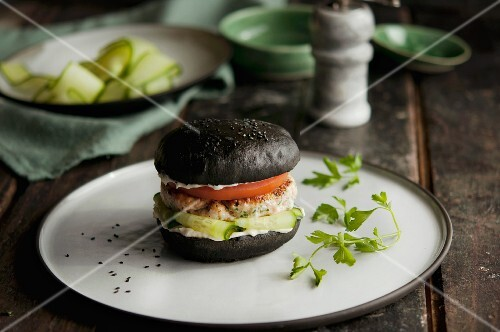 Salmon fillet on a black burger bun