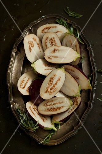 Halved baby aubergines on a silver tray (seen from above)