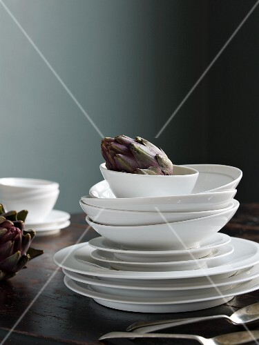 Stack of white plates and soup bowls on table