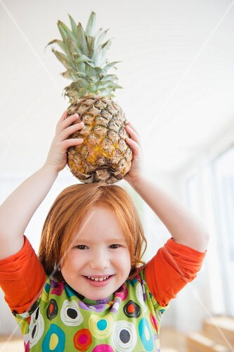 A little girl holding a fresh pineapple above her head