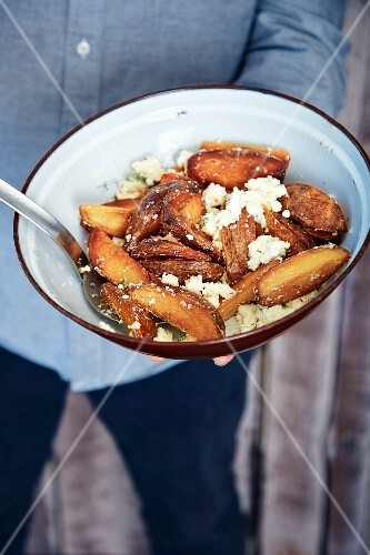 Fried potato wedges with feta cheese and thyme