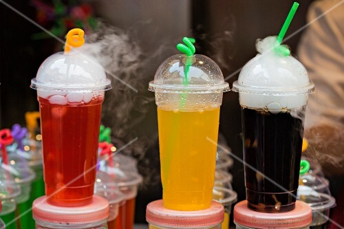 Coloured soft drinks in plastic cups on a market stand