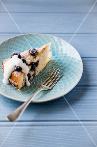 A slice of blueberry cake with yoghurt