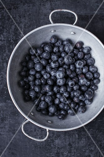 Freshly washed blueberries in an aluminium colander
