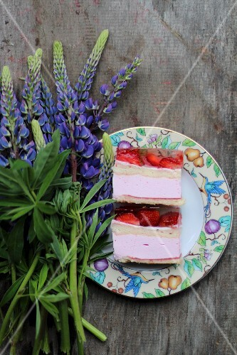 Two slices of strawberry cake on a plate next to lupin flowers