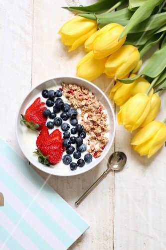 Muesli with yoghurt, blueberries and strawberries next to a bunch of yellow tulips