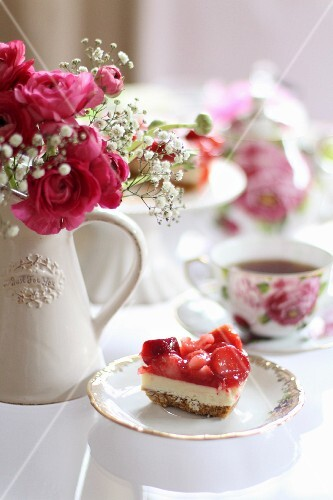 A slice of strawberry cake on a romantically laid table