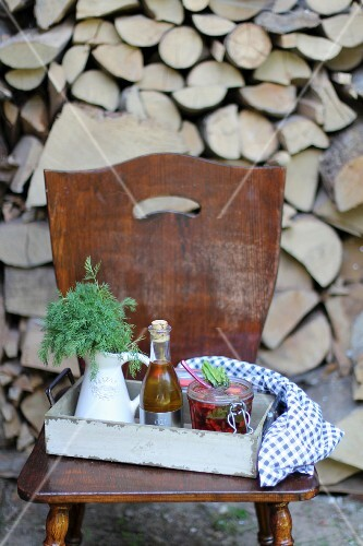 Soup in a flip-top jar, a bottle of oil and dill outside on a wooden chair