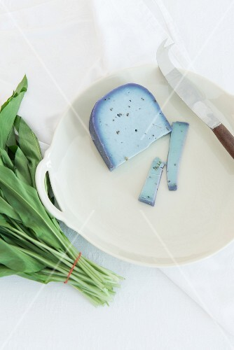 Lavender Gouda on a porcelain plate next to a bunch of fresh wild garlic