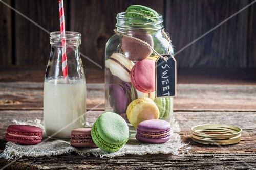 Colourful macaroons in a jar and next to a milk bottle