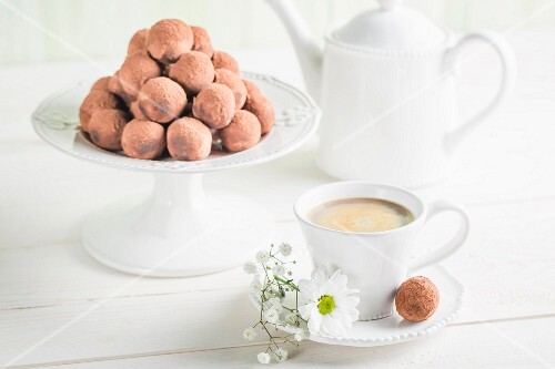Chocolate truffles on a white table with coffee