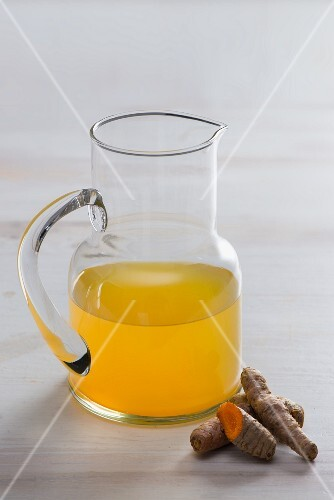 Fresh turmeric juice in a jug with turmeric roots on a white surface