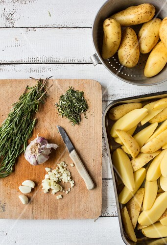 Ingredients for rosemary potatoes on a wooden chopping board and raw potato wedges in a roasting dish