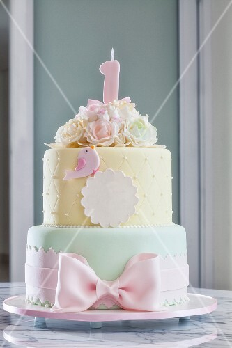 A festively decorated birthday cake in delicate pastel tones