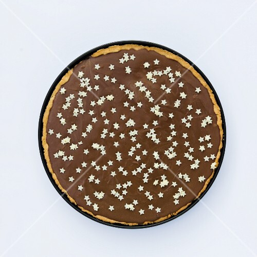 Tarte au chocolat decorated with small white stars (seen from above)