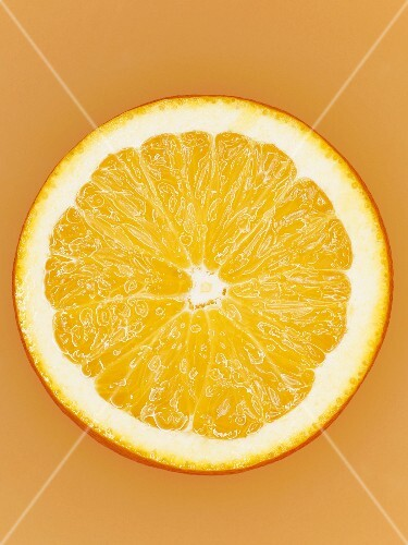 A slice of orange on orange surface, close-up