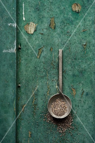 Chia seeds in a spoon on a rustic surface
