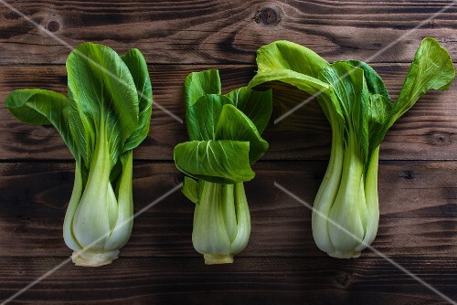 Three bok choy on a wooden board