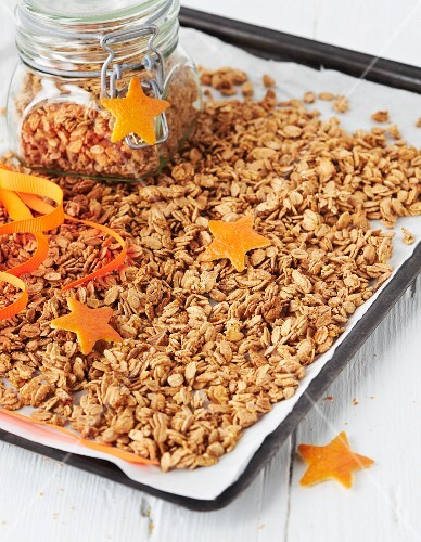 Crunchy orange muesli on a baking sheet and in a glass jar