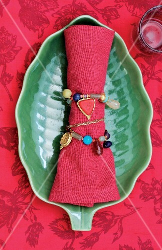 Red linen napkin tied with beaded chain on green leaf-shaped dish on red patterned tablecoth