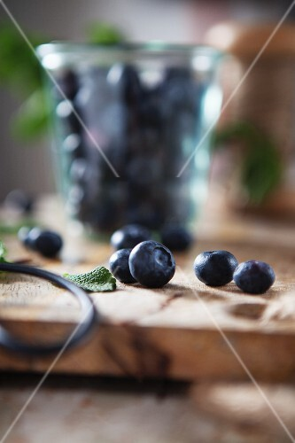 Fresh blueberries with mint and herb scissors on a wooden work surface