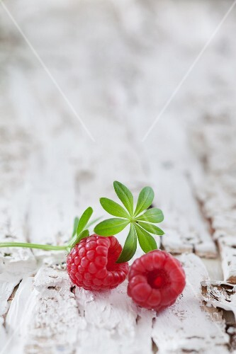 Two raspberries and a sprig of woodruff on a white wooden surface