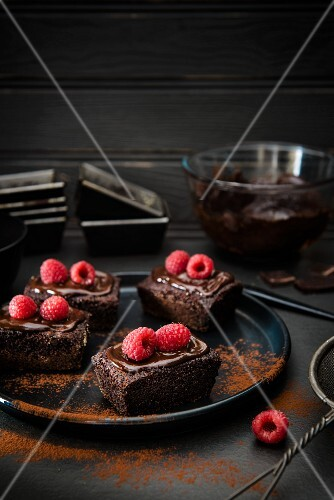 Mini chocolate cakes with raspberries and cocoa powder