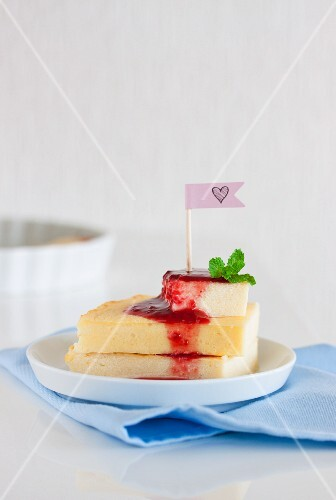 A stack of quark and semolina slices with raspberry sauce and mint leaves
