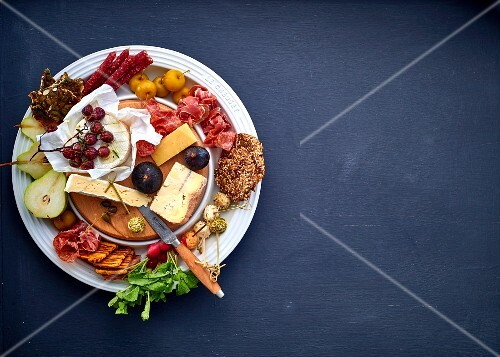 Cheese platter with fruit, vegetables and meats