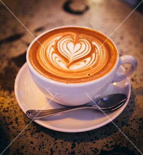 A cappuccino with a heart design in the milk from