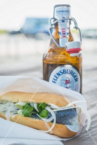 A fish roll and a bottle of beer outside on the table (Sylt, Germany)