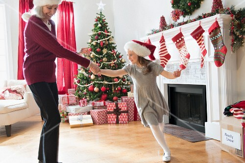 Grandmother and her granddaughter dancing in a living room decorated for Christmas