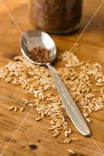 Oat seeds on a wooden surface with a spoon