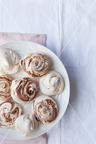 Meringues with and without chocolate swirls on a plate