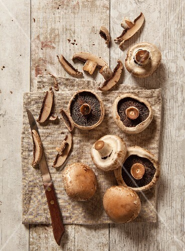 Fresh mushrooms, partially sliced, with an old-fashioned knife on a brown linen cloth