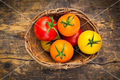 Red, yellow and orange tomatoes in a wicker basket on a wooden surface