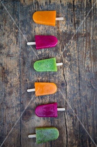 Various fruit ice lollies in a row on a wooden surface (seen from above)