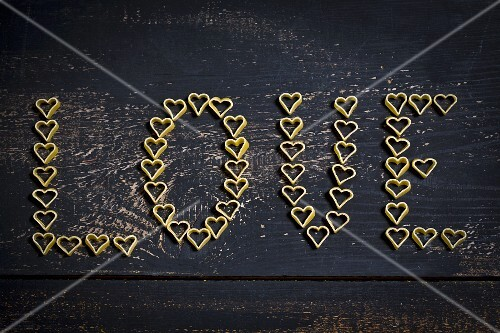 The word 'Love' spelt in heart-shaped pasta on a dark wooden surface