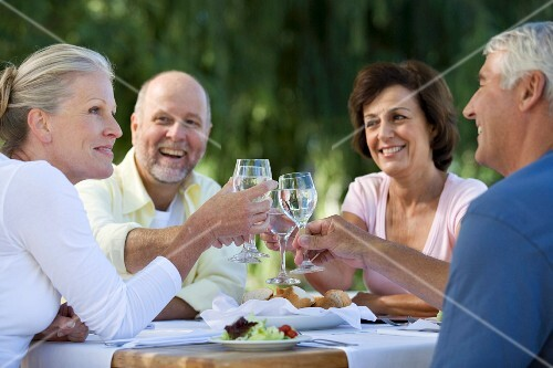 Four older people sitting outside at a table raising glasses