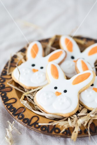 Easter bunny cookies on a wooden plate with straw