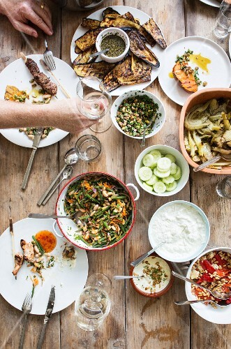 Grilled kebabs, aubergines, salad and sauces on a wooden table (seen from above)