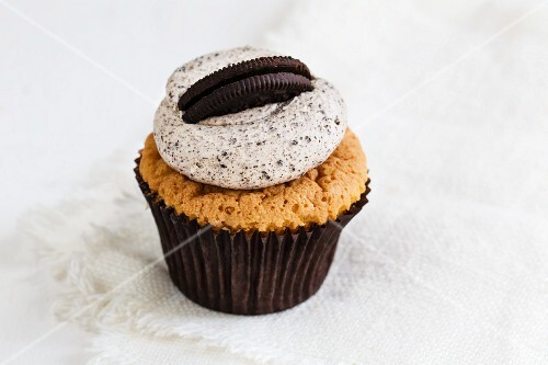 A cupcake decorated with coffee cream and an Oreo