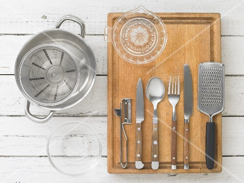 Kitchen utensils: a pot, a measuring jug, a citrus juicer, cutlery, a grater and a peeler