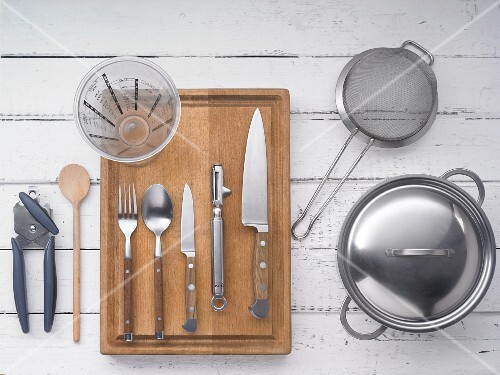 Kitchen utensils: a pot, a sieve, knives, cutlery, measuring jug and a tin opener