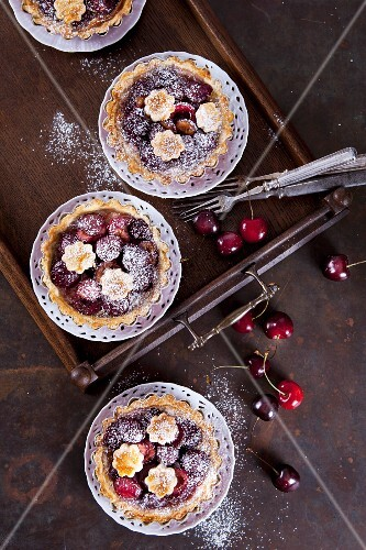 Mini shortcrust pies with cherries and icing sugar (seen from above)