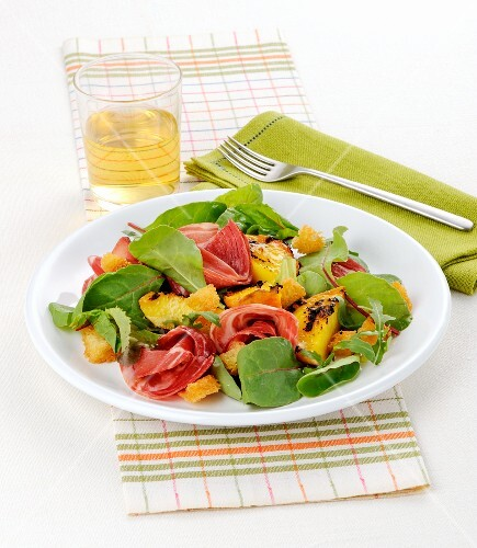 Salad with grilled peaches, beetroot leaves, ham and croutons