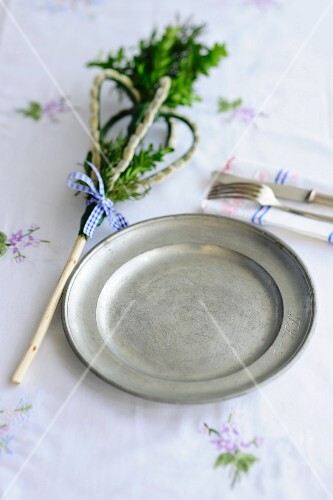 An Easter place setting with a pewter plate, cutlery and boxtree decoration